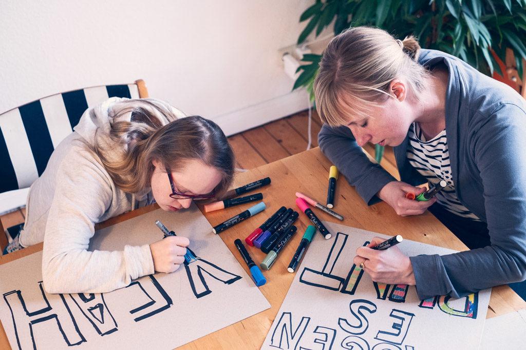 Neele und Lena von der Inklusiven WG Bremen malen Schilder. Wir mögen es bunt steht darauf, für ein buntes Miteinander aller Menschen. Das Foto ist von Daniela Buchholz.